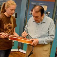 Bobby Osborne signs a mandolin for a student at the 2018 Bobby Osborne Mandolin Roundup - photo by Terry Vaught