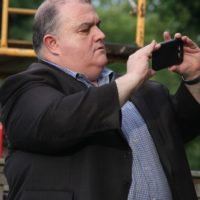 MC Tim Michaels snaps a photo at the August 2018 Gettysburg Bluegrass Festival - photo by Frank Baker