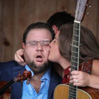 Sally Berry plants a kiss on her husband, Hunter, at the August 2018 Gettysburg Bluegrass Festival - photo by Frank Baker