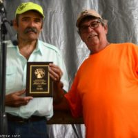 Tim Ellis accepts Hall of Fame plaque from Bill Warren at the 2018 Blissfield Bluegrass on the River - photo © Bill Warren