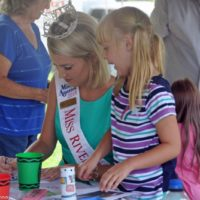 Haley Petrowski, Miss River Raisin 2018, helps out at the Kid's Corner at the 2018 Blissfield Bluegrass on the River - photo © Bill Warren