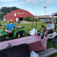 """Rich James and Shawn Szirbik, long time Podunk volunteers, check in on campers and """"concierge"""" others to their sites at the 2018 Podunk Bluegrass Festival - photo by Dale Cahill"""