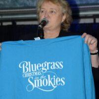 Host Lorraine Jordan shows off this year's T-shirt at 2018 Bluegrass Christmas in the Smokies - photo © Bill Warren