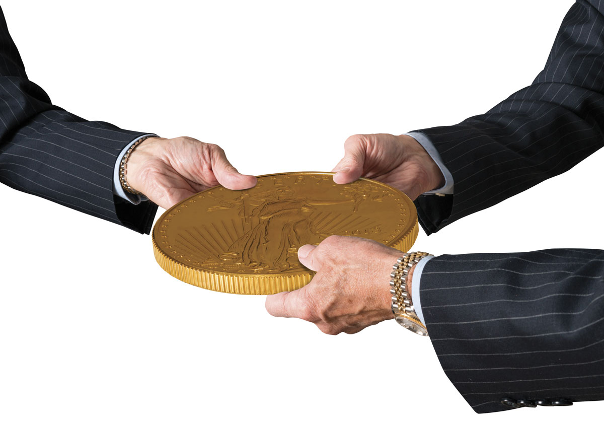 Hands of three financial traders gripping large Gold American Eagle coin
