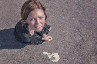 a woman looking up angrily at the camera as her unfinished icecream cone melts on the ground