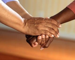 two people clasping each others' hands in support
