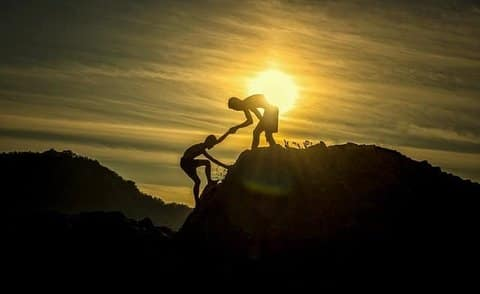 one man helping another climb up a mountain