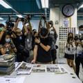 Le directeur général de l'Apple Daily Cheung Kim-hung (c) lit les titres de la Une avant qu'il parte à l'impression, le 17 juin 2021 à Hong Kong