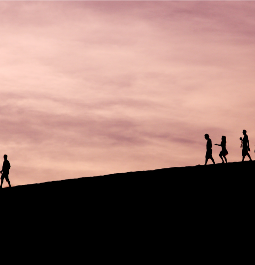 One person leading a group in front of a rosy sunset
