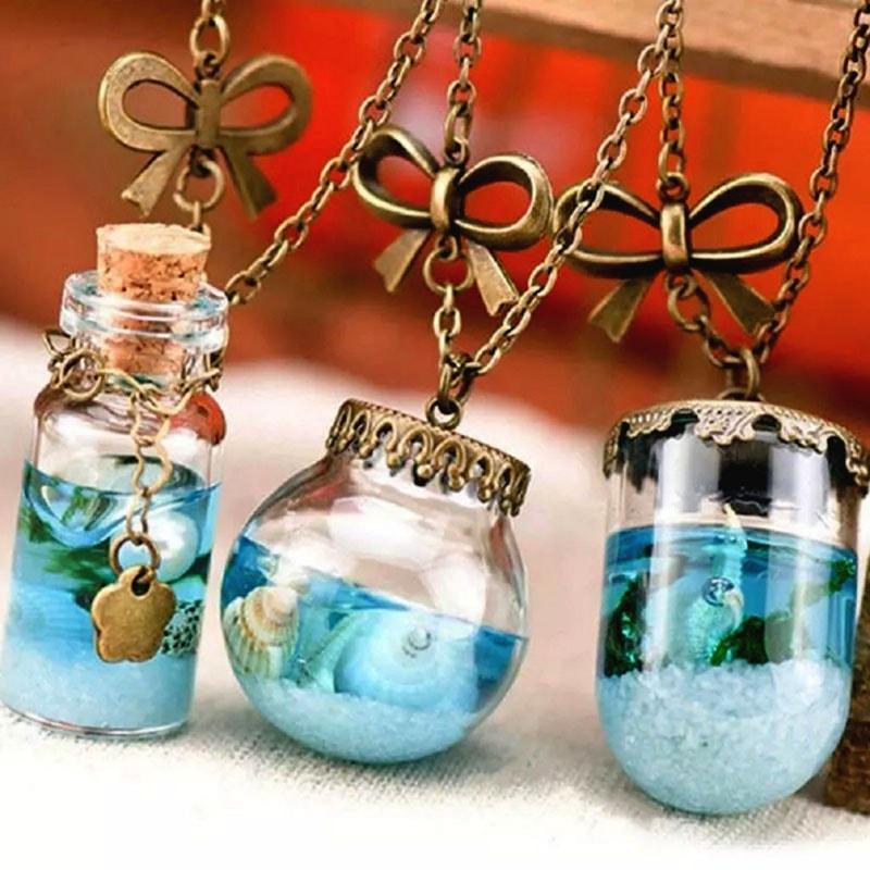 frasco con conchas de mar y arena en collar para recuerdo de bautizo