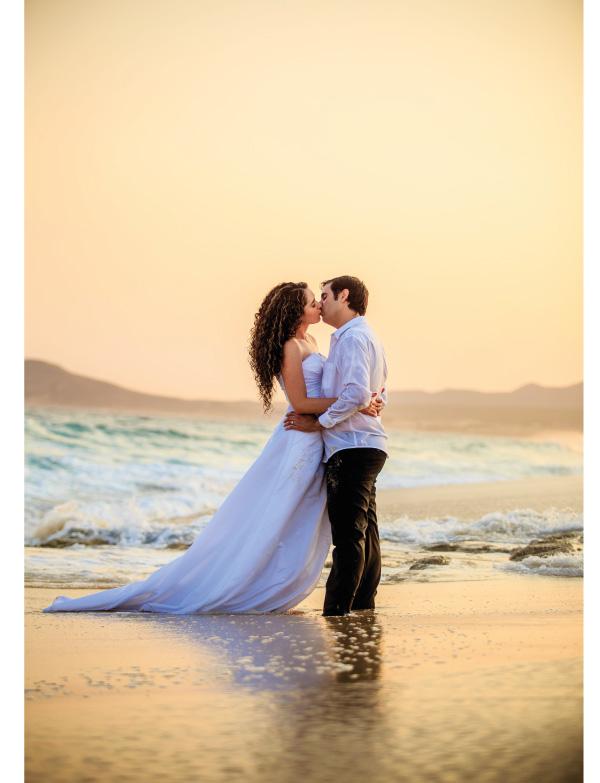 pareja frente al mar besándose y abrazándose