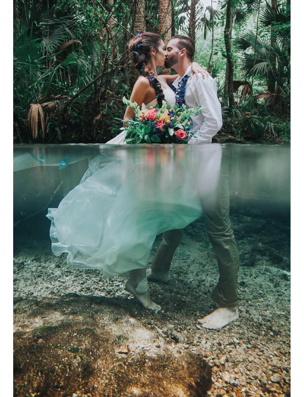 pareja besándose parados sobre un lago