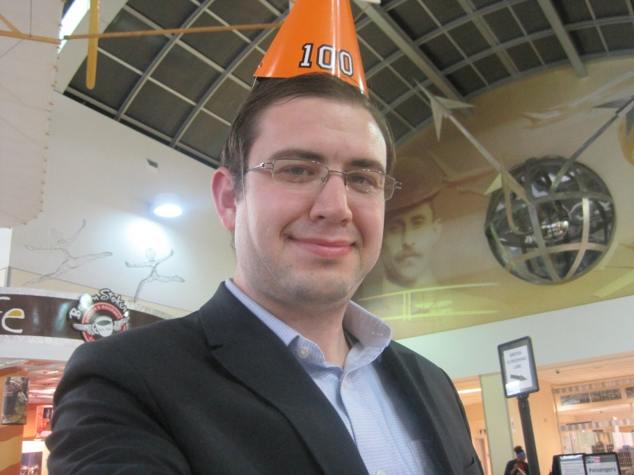 Photo of Paul at the Dayton airport wearing a party hat with the number 100 on it