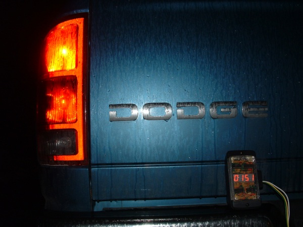 Rear end of a Dodge Ram pickup truck, with the turn signal lit, and a four-digit counter sitting on the bumper