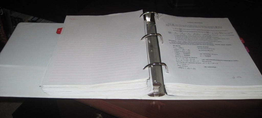 Photo of a 3-inch binder filled with homework assignments