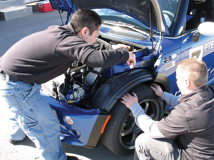 Aaron Ogawa and Corey Bedortha (kneeling) adjust the camber on our MINI Cooper S test car.