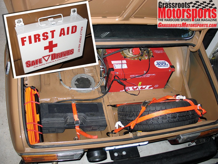 Our trunk showcases the ATL fuel cell, our tool kit and the spare. We shielded our newly painted cage with Lamin-x film. A first aid kit is a rally essential.
