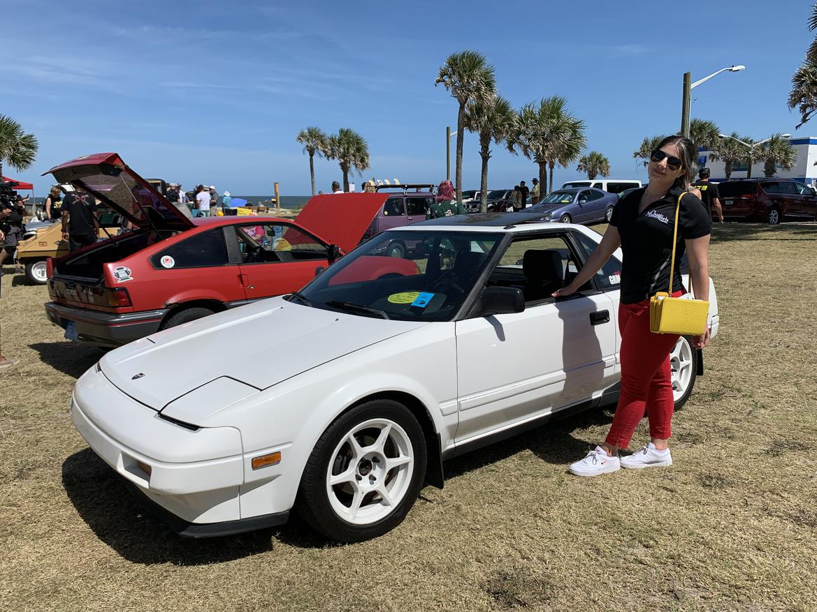 woman standing next to a white 1985 MR2 AW11 with palm trees in the background