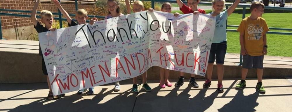 Photo of kids in front of Horace Mann Elementary schools with banner