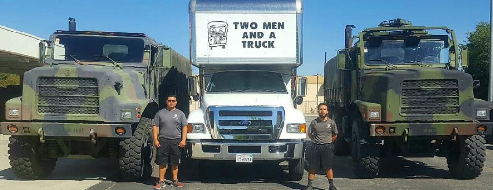 movers standing next to military trucks