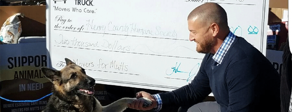 two men and a truck presenting the humane society with a large size donation check
