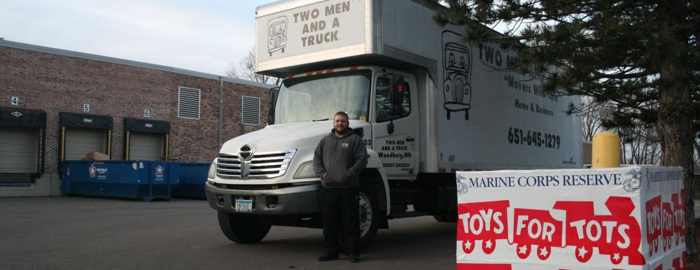 two men and a truck mover standing by truck with toys for tots box