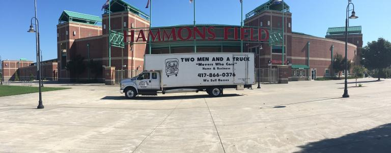 two men and a truck parked in front of hammons field