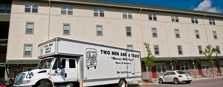 Two men and a truck parked in front of an apartment
