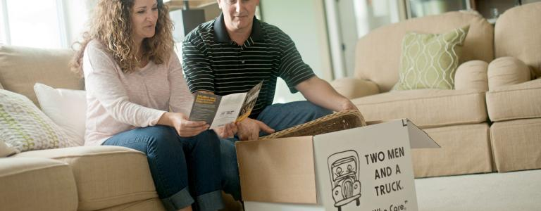 couple looking at two men and a truck company brochure