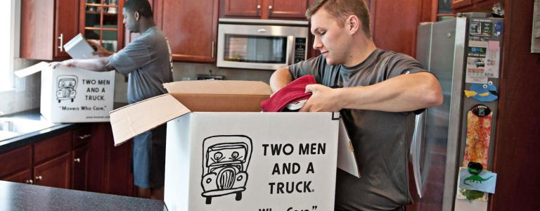 two movers packing boxes in a kitchen