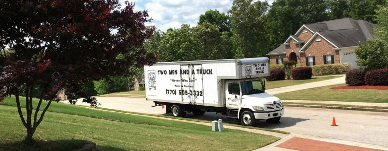 Two men and a truck company moving truck for both dallas and douglasville parked in a neighborhood