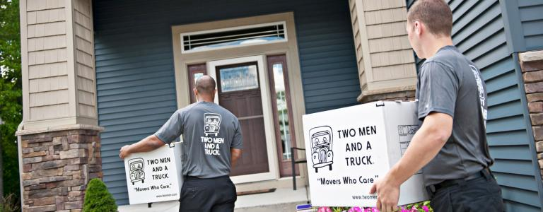 two men and a truck movers carrying boxes into a house