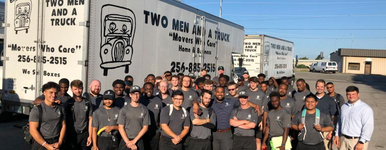 two men and a truck moving team standing in front of fleet