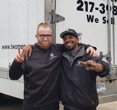 smiling movers standing in front of a truck