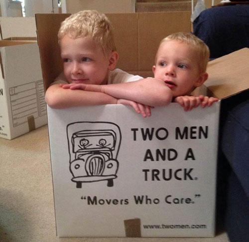 two kids sitting in a two men and a truck moving box