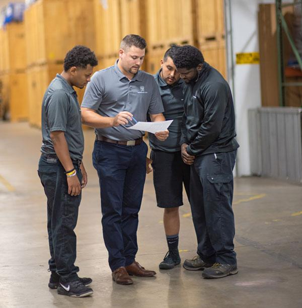 a training manager holding a clipboard teaching new employees