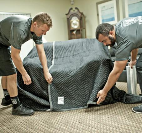 two men and a truck movers wrapping furniture for protection