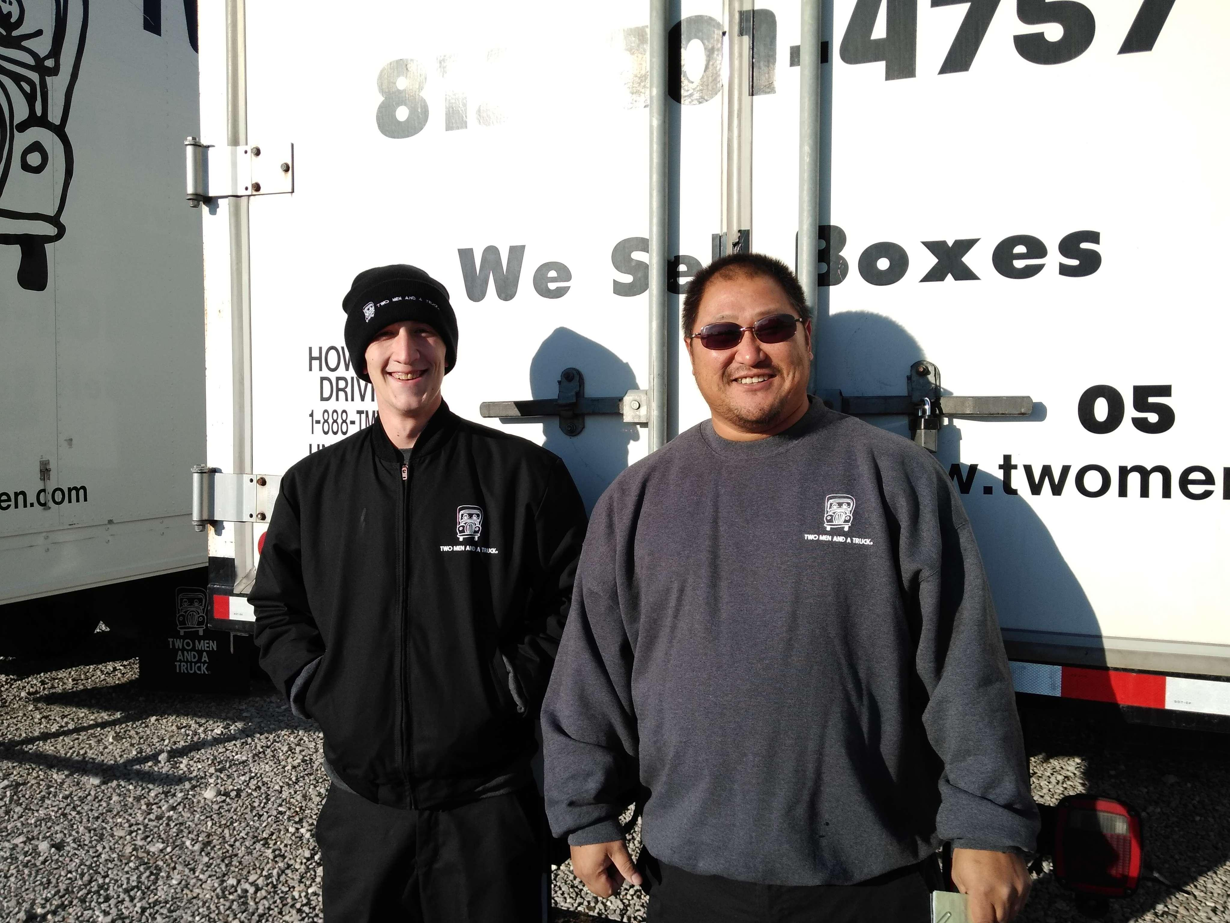 Two movers standing in front of the back of the moving truck smiling.