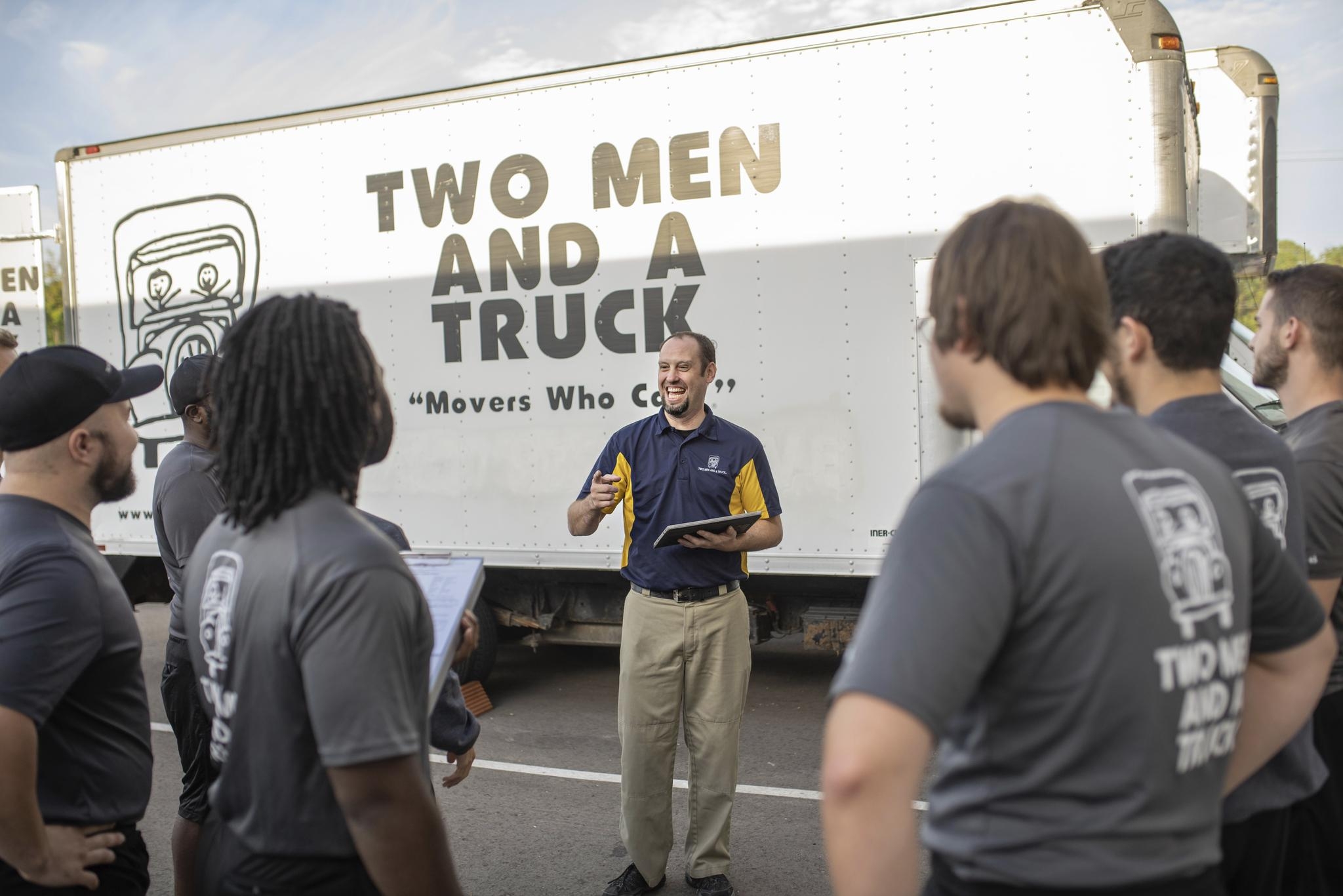 Manager giving instructions to the move team outside beside a truck