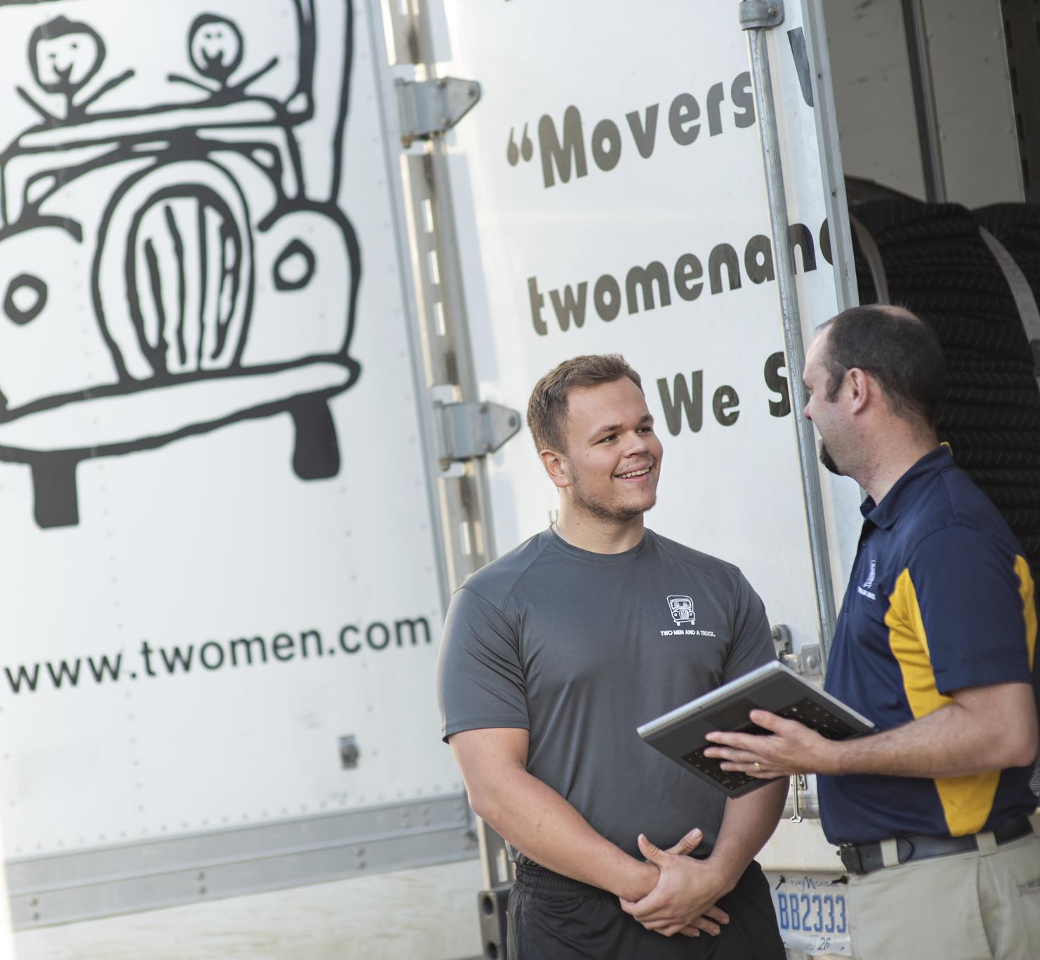 Two men standing beside a moving truck talking