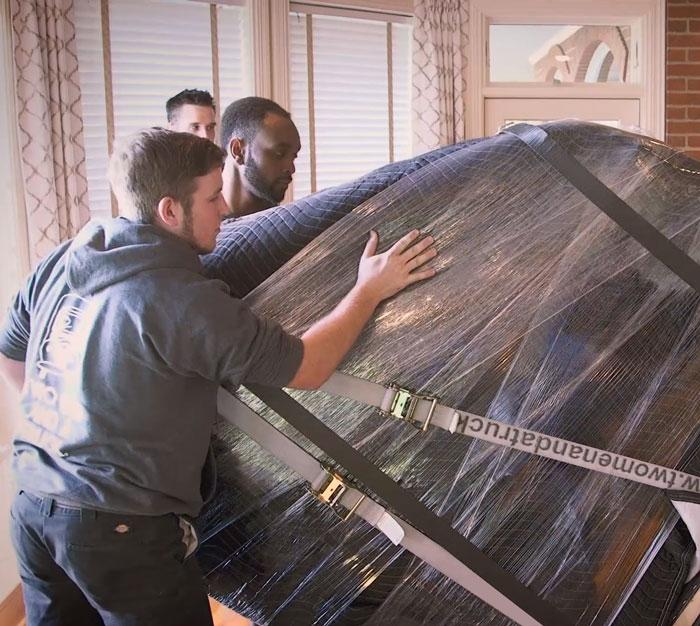 movers transporting a piano
