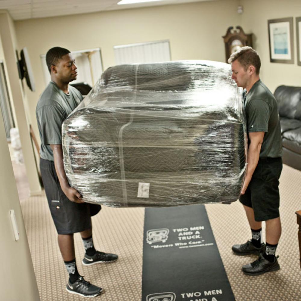 movers carrying a stretch wrapped chair