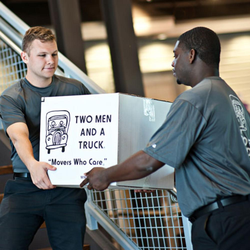 two movers handing off a box from one to the other