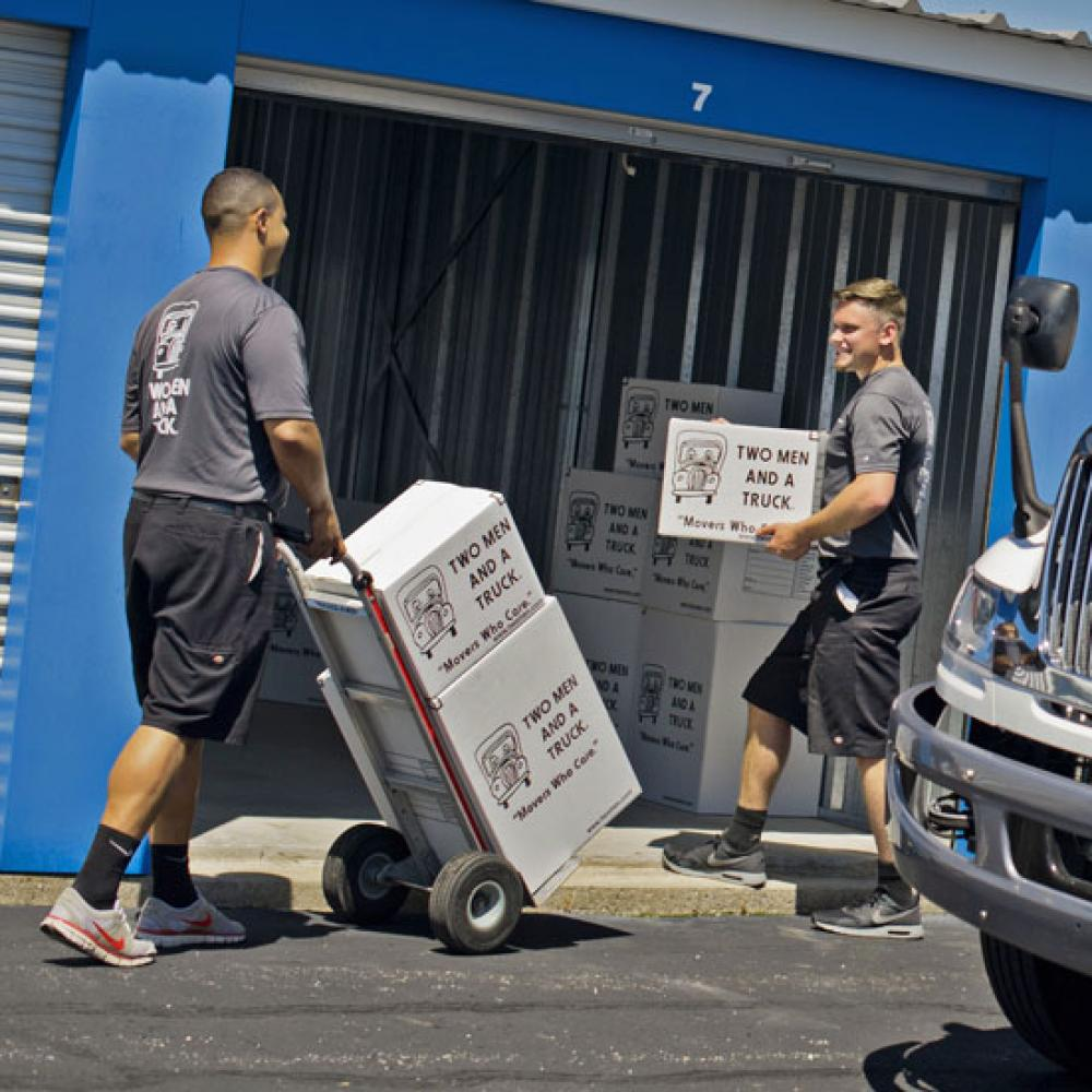 movers with two men and a truck unloading a storage facility