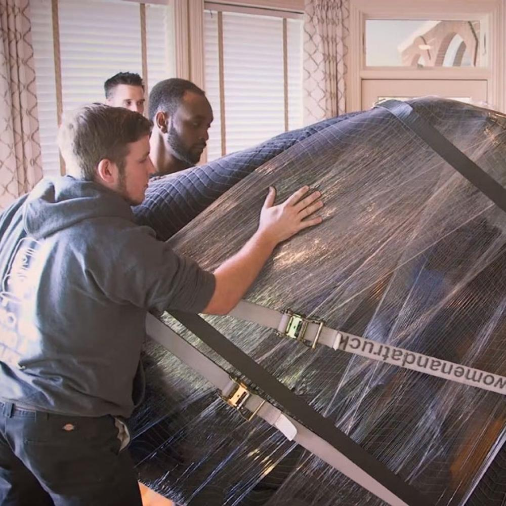 Movers preparing a piano for relocation