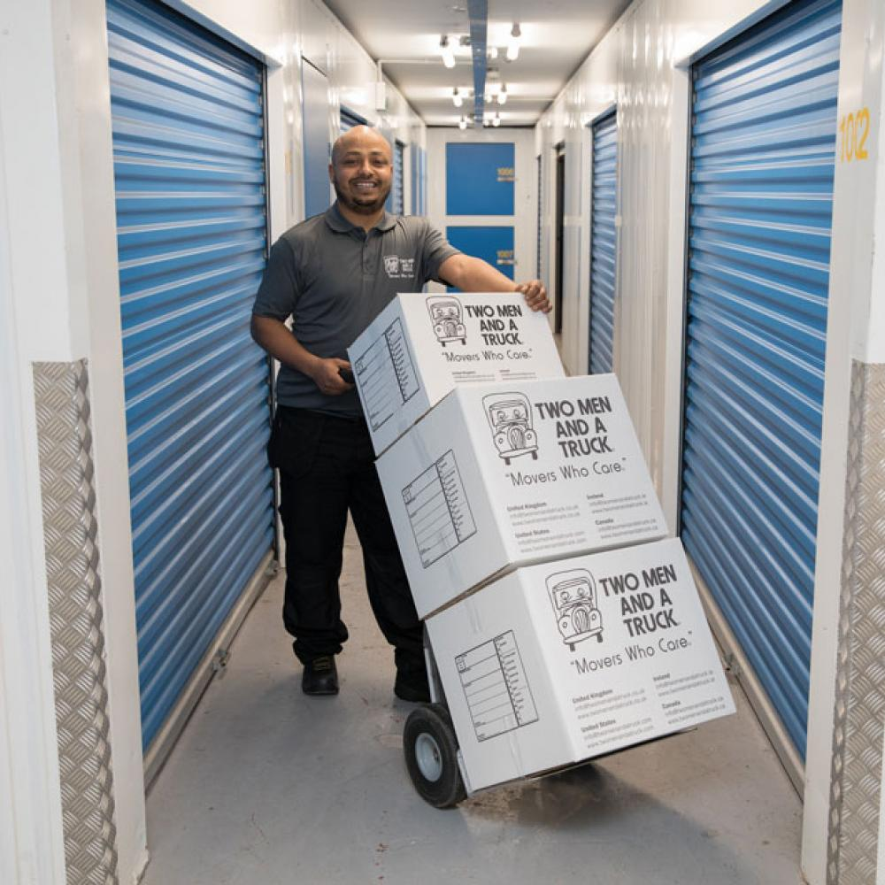 mover in a storage facility carrying two men and a truck branded boxes on a dolly