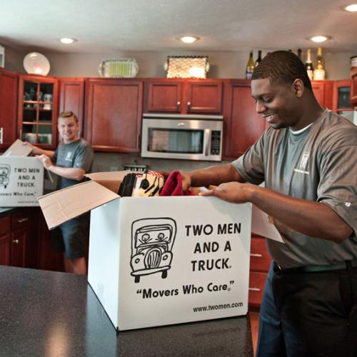 two movers packing up kitchen items into a box