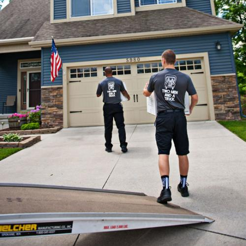 movers carrying boxes to a house