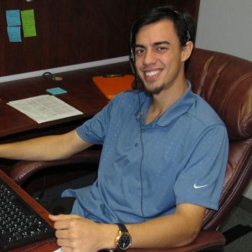 Customer Service Rep, Alex Petz, sitting as his desk assisting customers.