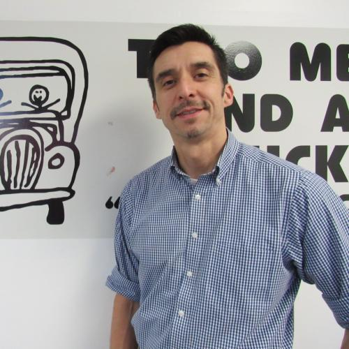 Office Assistant, Davis Jao, standing in front of our Truckie logo!